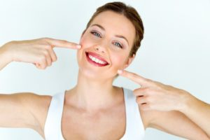 Woman pointing at her teeth after teeth whitening in Trumbull